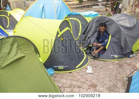 KOS, GREECE - SEP 27, 2015: Unidentified war refugee near tents. More than half are migrants from Syria, but there are refugees from other countries - Afghanistan, Pakistan, Iraq, Iran, Mali, Eritrea.