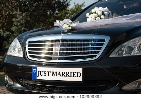 Black car with a text: Just Married. Bunch of flowers