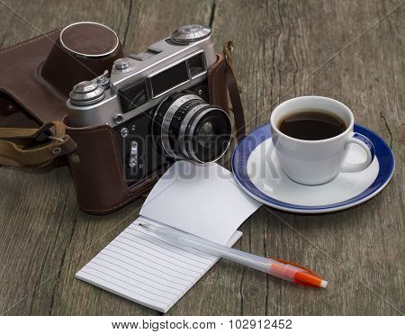 The Old Camera, Coffee And Notebook With The Handle On A Wooden Table