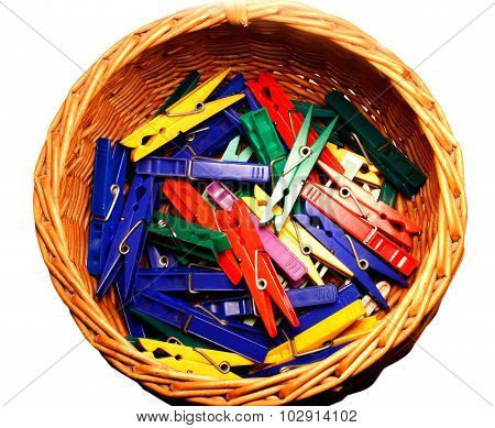 Lots of colourful clothes pegs in a woven basket