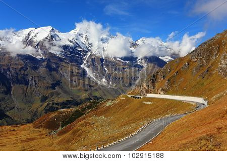 Famous picturesque views of the road in Austrian Alps - Grossglocknershtrasse. Ideal highway winds high in the mountains. The highest mountain peaks covered with fresh snow