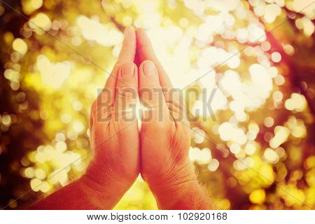 Praying hands, cross shaped lens flare.