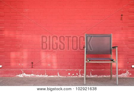 Chair and lamp against brick wall