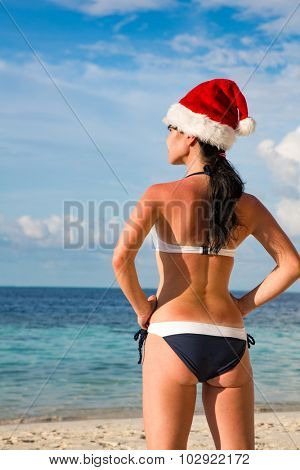Christmas vacation - woman in santa hat on the beach