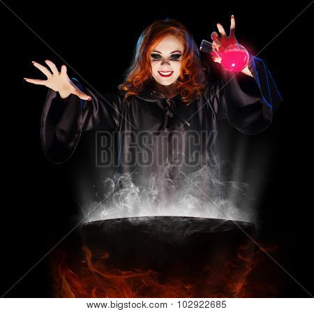 Young witch with potion and cauldron isolated