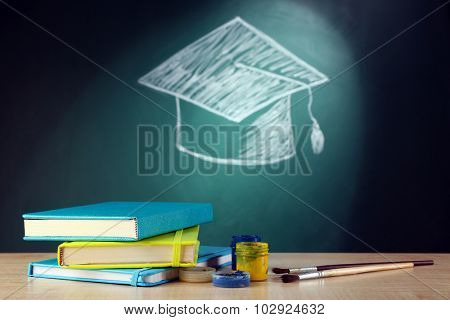 Stack of books and bachelor hat drawing on blackboard background