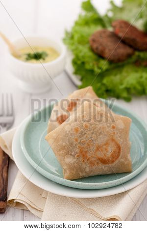 burrito wraps or tortilla wrapped with meat and beans and served on a plate