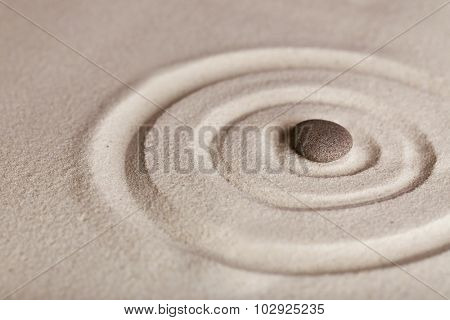 Zen garden with stone on sand background