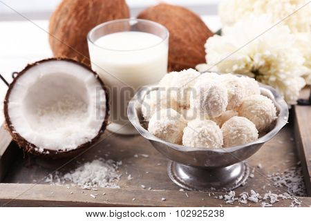 Homemade sweets in coconut flakes and fresh coconut on tray, close-up