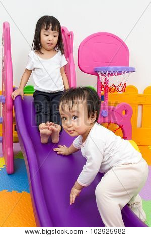 Asian Chinese Little Sister And Brother Playing On The Slide