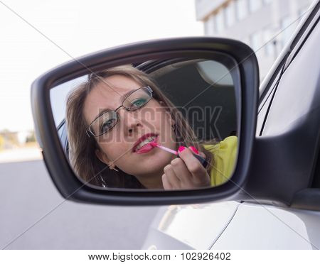Woman In  Car, Looking At Mirror And Painting Her Lips