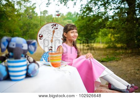 Girl sits at table and holding a cup of tea. Alice in Wonderland concept
