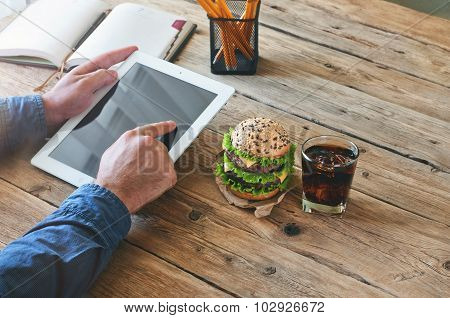 Man Working With A Tablet Computer At A Wooden Table