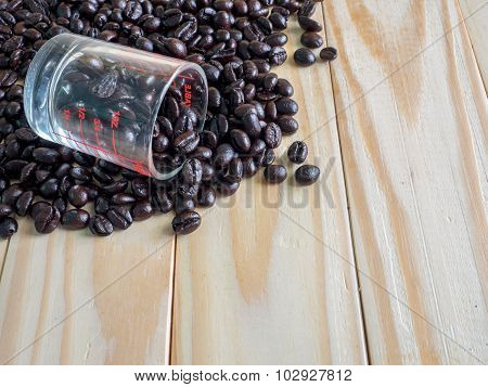 Coffee beans and a measuring cup on wooden board