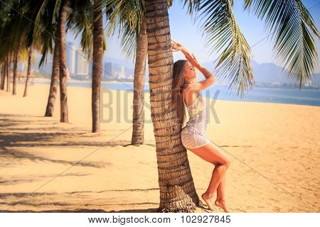Blonde Girl In Lace Closeup Leans Back On Palm Smiles On Beach