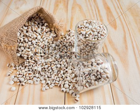 Millet in glass and sack on wood Background