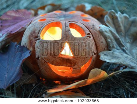 Candlestick pumpkin with a burning candle inside, among autumn fallen leaves, symbol of Halloween