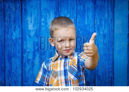 Portrait Of Happy Joyful Beautiful Little Boy Gesturing Thumb Against The Blue Wall