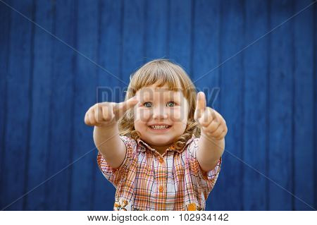 Portrait Of Happy Joyful Beautiful Little Girl Gesturing Thumb
