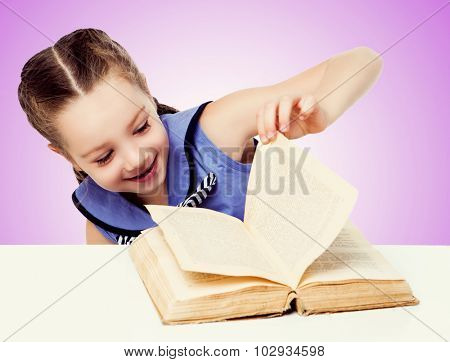 happy smiling girl with a book by the table, against pink studio background