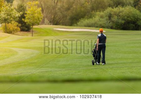 Golf man player holding trolley with clubs