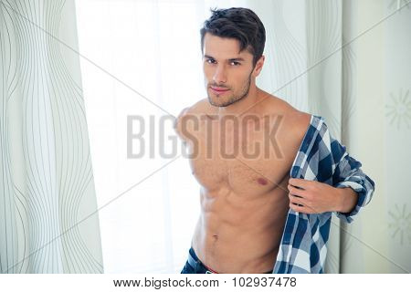 Portrait of a handsome man dressing shirt and looking at camera