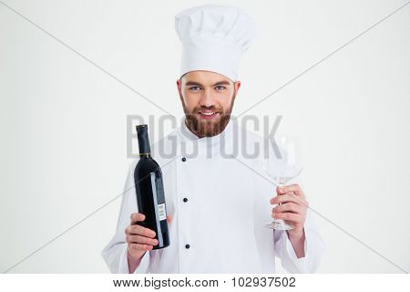 Portrait of a smiling male chef cook holding bottle of wine and wineglass isolated on a white background