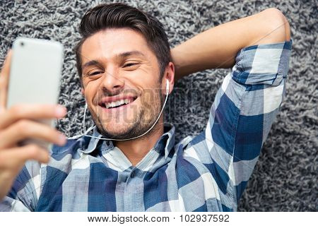 Portrait of a smiling man using smarpthone on the floor at home