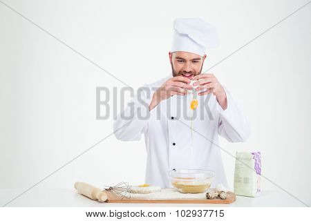 Portrait of a happy man breaking eggs into a bowl for baking isolated on a white background