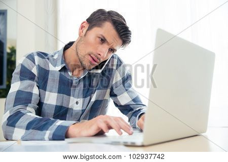 Portrait of a man paying his bills with laptop while talking on phone at home