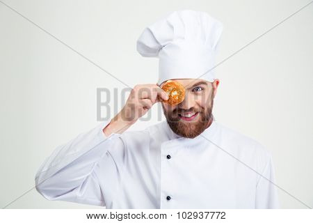 Portrait of a smiling male chef cook covering his eye with pancake isolated on a white background
