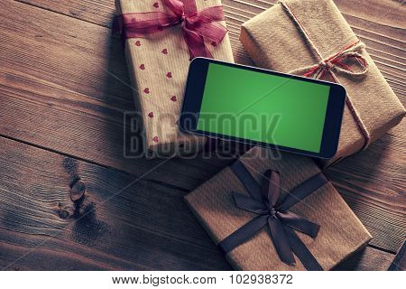 Black smart phone on a heap of gift boxes. Clipping path included.