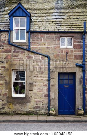 Rural cottage detail. Old stone cottage with blue window and door.