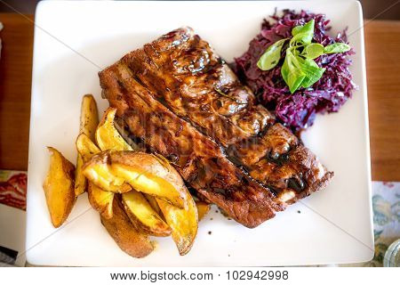 Barbecue Pork Ribs As Main Dish At Restaurant. Pork Delicacy With Delicious Barbecue Sauce, Parsley,
