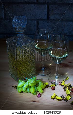 Crystal carafe of white wine, two glass, grapes on wooden table and gray bricks background