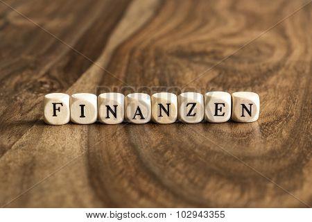 German Word Finanzen On Wooden Cubes