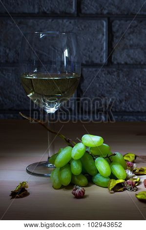glass of white wine and grapes on wooden table and gray bricks background