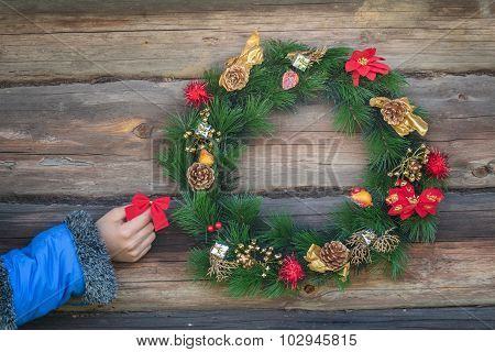 Human hand holding red bow and hanging on rustic log cabin wall with Christmas wreath