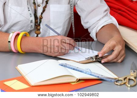 Close-up Of Adult Female Dressmaker Drowing Some Clothing Design