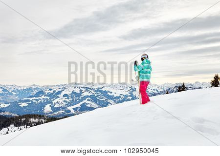 Back view of female snowboarder wearing colorful helmet, blue jacket, grey gloves and pink pants standing with snowboard in one hand against alpine mountain landscape - extreme sports concept