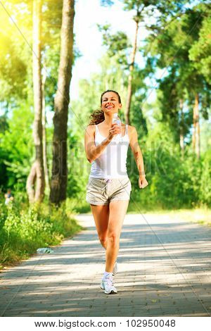 Woman running in the park. Young sporty lady jogging with bottle of water outdoors. Workout. Healthy lifestyle. Full length portrait. Vertical photo