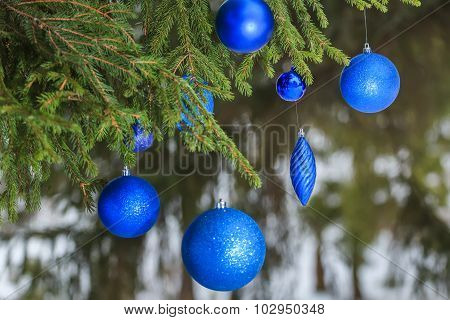 Outdoor Christmas turquoise sparkle bauble ornaments hanging on snowy spruce twig