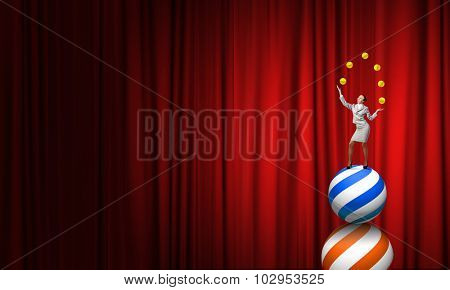 Young businesswoman standing on ball juggling with balls