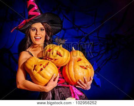 Happy witch holding orange pumpkin. Net background.