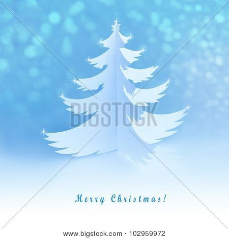 White handmade paper cut christmas tree with magic defocused snowflakes