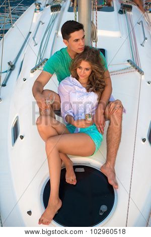 Lovers drinking champagne on a sailing yacht.