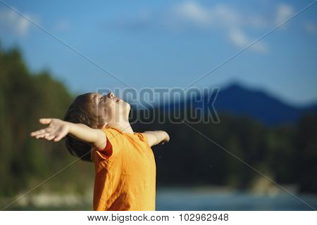 the boy raised his hands up nature