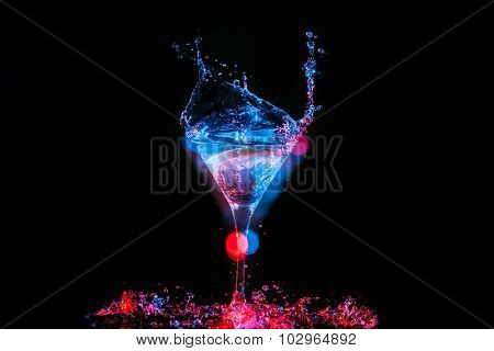 Bright cocktail with lemon in glass and splashing water on dark background