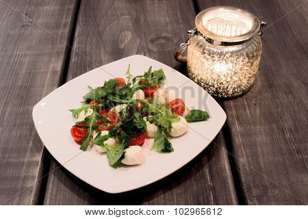Green Salad With Arugula, Tomatoes, Cheese Mozzarella Balls On Plate, On Wooden Background