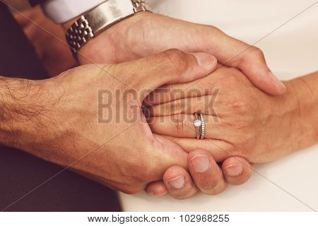 Close-up with bride and groom holding hands